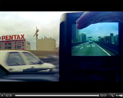 Image of a city car journey, with a playback of a second journey shown on a handheld camera in the passenger seat